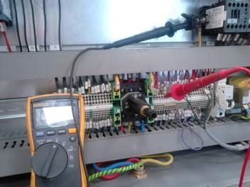 Multimeter in control panel with red and black probes