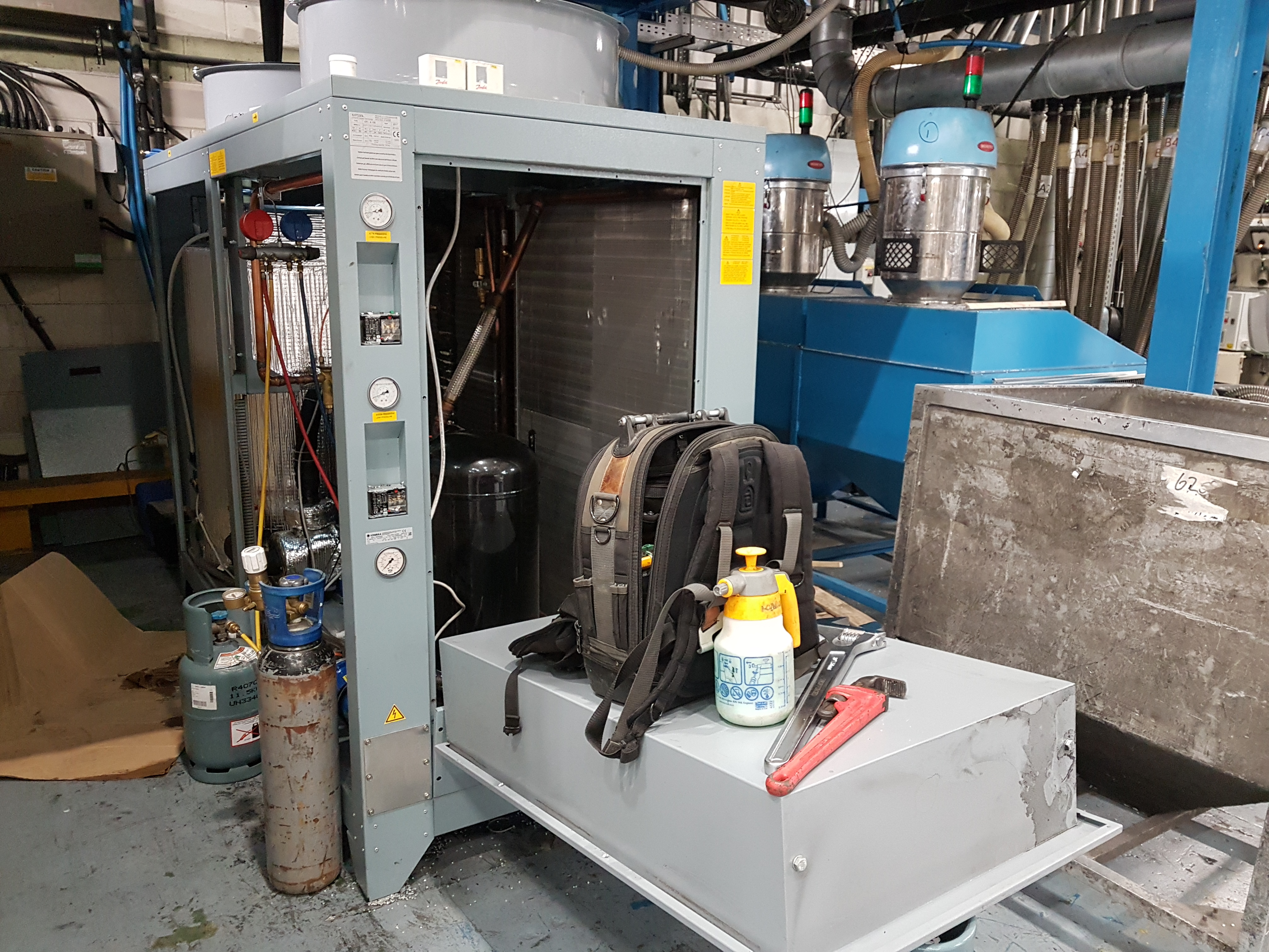 Industrial process chiller being serviced, maintained and repaired with tools on top of the panel