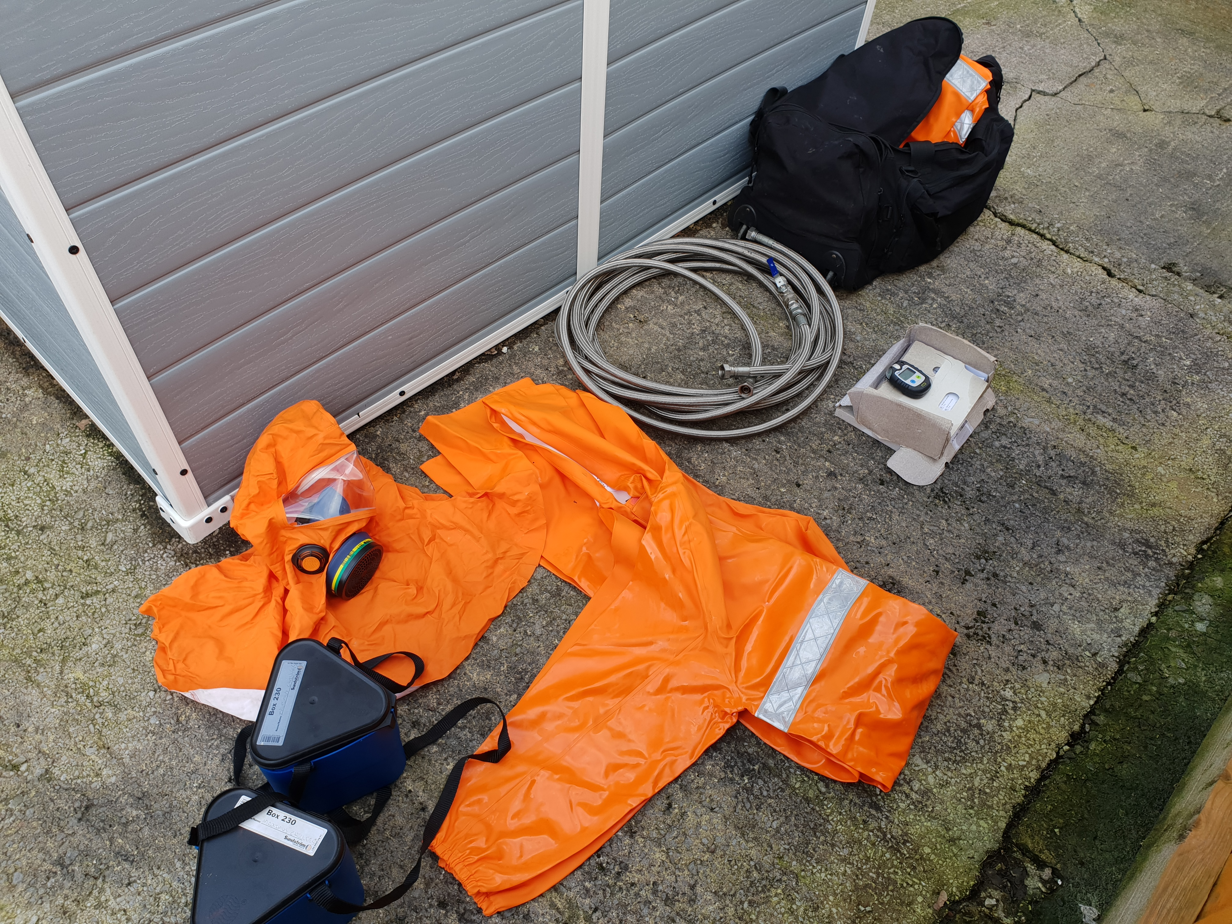 Orange chemical suit and charging hose for ammonia chiller service maintenance and repair