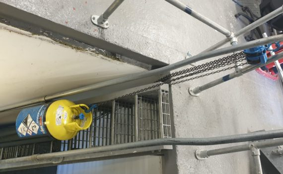 Ammonia refrigerant cylinder being winched up a cat ladder using a block and tackle
