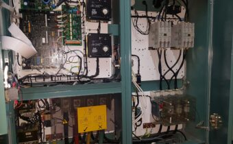 Green chiller panel with doors open, showing contactors and PCBs during water chiller maintenance