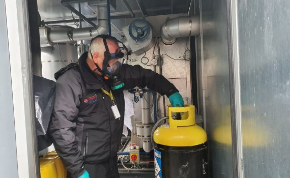 Engineer carrying out process chiller service with yellow and black cylinder