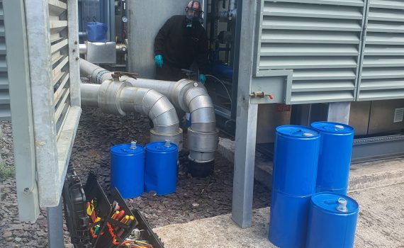 An engineer filling blue oil drums during industrial chiller maintenance