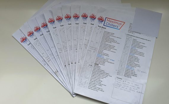 A pile of completed chiller maintenance checklists on a table
