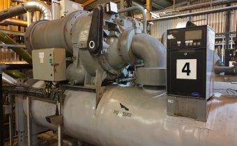 Grey shell & tube chiller evaporator being maintained with centrifugal compressor above