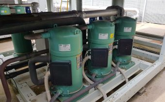 6 green Bitzer scroll compressors being maintained in a chiller