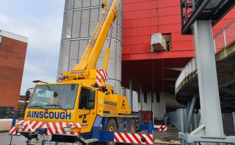 Boxed, shell and tube chiller condenser being lifted into a building with a crane