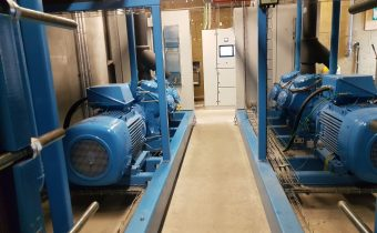 Two blue open drive Vilter reciprocating chiller compressors being maintained in a plant room